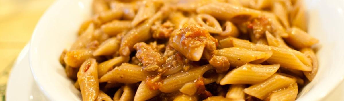 Pennette integrali con paté di olive, pomodorini e pan grattato